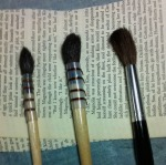The synthetic brush (black handle, top) holds considerably less water than the smaller squirrel-hair brush.
