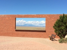 It's not a painting; it's an open space in the wall, overlooking Arizona's desert. Beyond is the Bar-T-Bar ranch, with the San Francisco mountain range in the background.